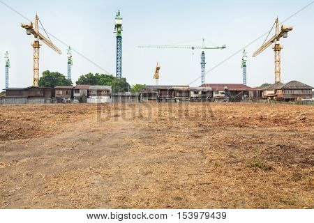 crane construction in front of the village with vacant land