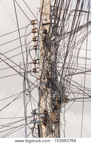Electricity post with many electrical cables that run in different directions