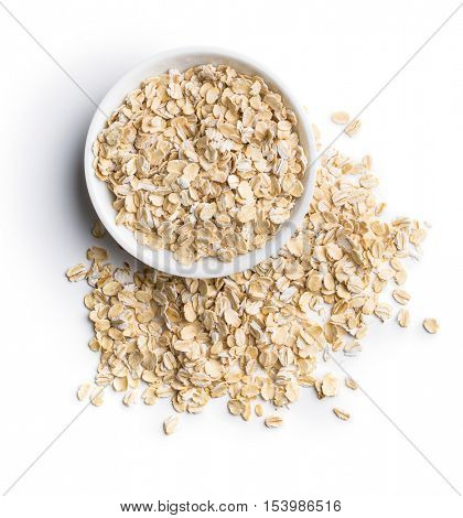 Dry rolled oatmeal in bowl isolated on white background. Top view.