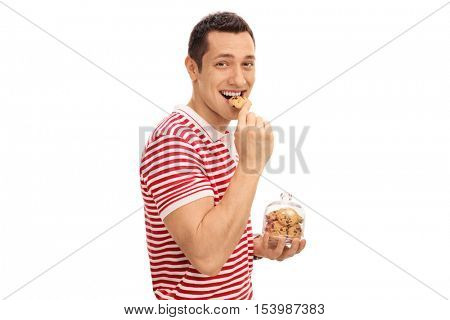 Young guy eating a cookie and holding a cookie jar isolated on white background