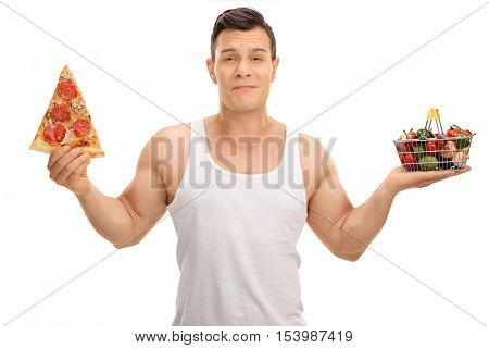 Indecisive young man holding a small shopping basket full of fruits and vegetables and a pizza slice isolated on white background