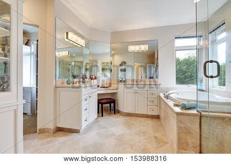 Master bathroom interior with beige tile floor double sink bath tub. Northwest USA