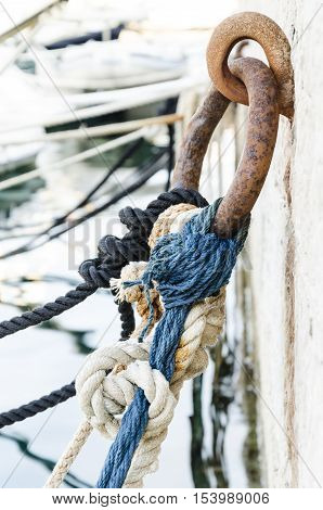 details of coloured ropes knotted to a rusted metal ring