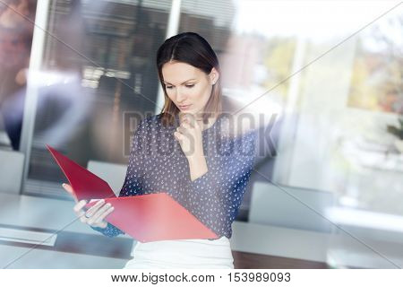 Young businesswoman with hand on chin reading file in office