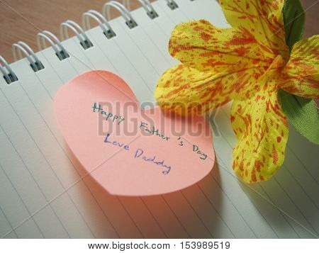 Happy father 's day love daddy handwriting on post it with heart shape, opened notebook with handmade flower
