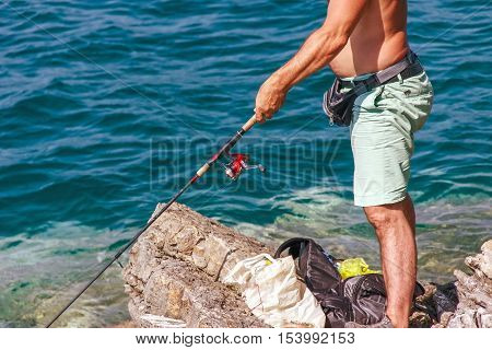 Man Catches A Fish, Standing On The Shore, Sunny Day Fishing At Sea