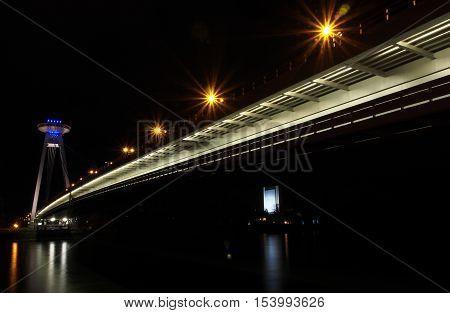 Night photography of iluminated city road bridge over river Danube in Bratislava