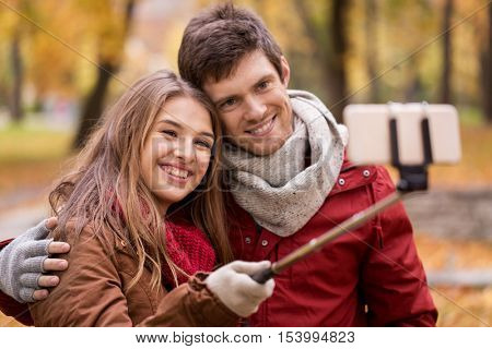 love, technology, relationship, family and people concept - happy smiling couple taking picture by smartphone selfie stick in autumn park