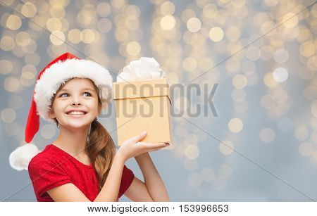 christmas, people, children and holidays concept - smiling girl in santa helper hat with gift box over lights background