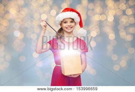 christmas, people, holidays and magic concept - smiling girl in santa helper hat with gift box and magic wand over lights background