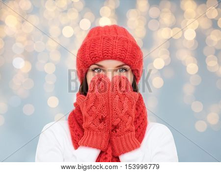 christmas, holidays, winter and people concept - surprised woman in hat, muffler and mittens over lights background