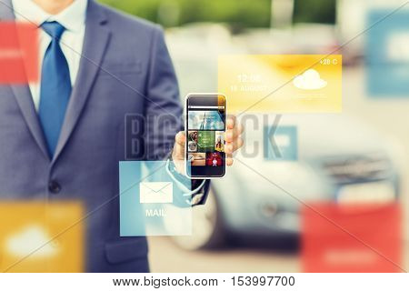 transport, business trip, mass media, technology and people concept - close up of man showing web pages on smartphone screen on car parking