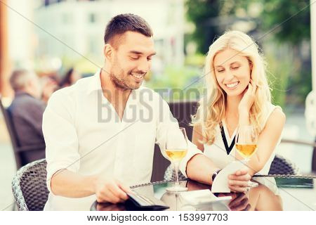 date, people, payment, holidays and relations concept - happy couple with wallet and wine glasses looking at bill at restaurant terrace