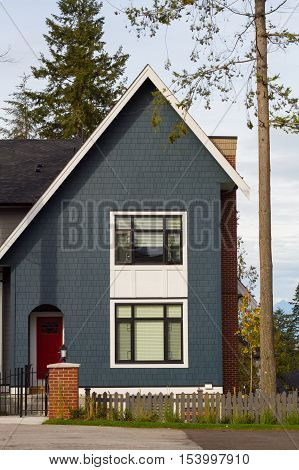 A brand new blue house with a slanted roof and a red door.