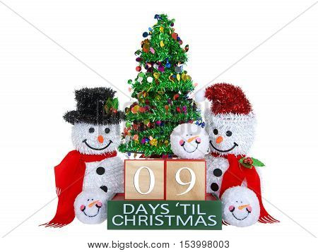 09 Days until Christmas light beech wood blocks with red trim on a green base with tinsel christmas tree mr and mrs snowman and snowball snowmen heads isolated on a white background.