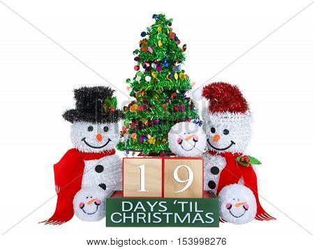 19 Days until Christmas light beech wood blocks with red trim on a green base with tinsel christmas tree mr and mrs snowman and snowball snowmen heads isolated on a white background.