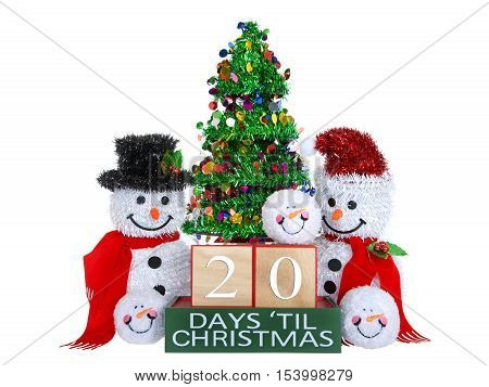 20 Days until Christmas light beech wood blocks with red trim on a green base with tinsel christmas tree mr and mrs snowman and snowball snowmen heads isolated on a white background.