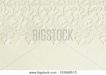 White embroidered lace on white wooden background