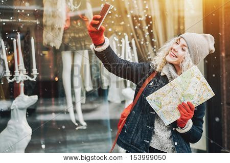 Young blond curly female tourist in warm clothes and red gloves with London map smiling and making selfie winter city blurred facade with flare on the background