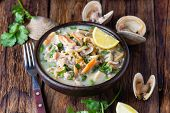 Latin American food. Seafood shellfish ceviche raw cold soup salad of seafood shellfish almejas, lemon, cilantro onion in clay bowl on wooden background. Traditional dish of Peru or Chile poster