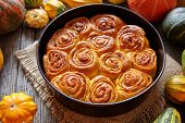 Cinnamon pumpkin dough bun rolls spicy traditional Danish baked vegan sweet fall treat cake holiday dessert swirl bread pastry food with raw pumpkins on vintage wooden table background. poster
