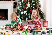 Happy little children in matching pajamas playing with Christmas presents - wooden toy railroad and car. Family Xmas morning in decorated living room with kids gifts fireplace and Christmas tree. poster