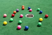 A number of brightly colored golf balls scattered around the hole on a practice putting green. poster