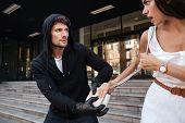 Man thief in black hoodie stealing woman bag on the street poster