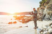 Young man preparing speargun for underwater fishing at sunset in italy - Male hunter getting ready for hunting wearing camouflage weatsuit - Extreme sport and hobby concept - Warm vintage filter poster