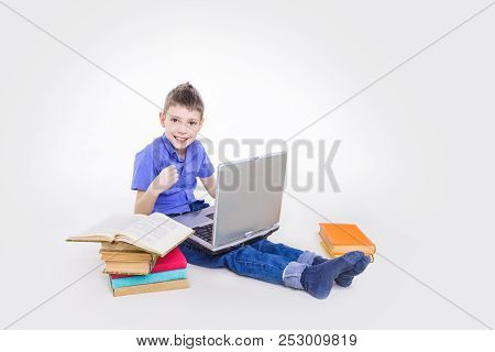 Portrait Of Cute Teen Schoolboy Sitting Near Books And Typing On Laptop Keyboard. Happy And Surprise