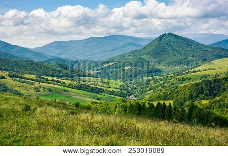 Beautiful Countryside In Mountains. Village In The Valley And Agricultural Fields On Hill Sides. Won