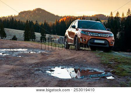 Apuseni, Romania - Oct 15, 2017: Orange Suzuki Vitara Suv On A Country Road In Mountains At Sunrise.