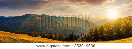 Panorama Of A Mountainous Landscape With Rainbow. Grassy Meadow Down The Hill In To The Forest. Love