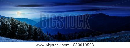 Panorama Of A Mountainous Landscape At Night In Full Moon Light. Grassy Meadow Down The Hill In To T