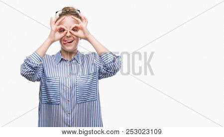 Young blonde business woman doing ok gesture like binoculars sticking tongue out, eyes looking through fingers. Crazy expression.