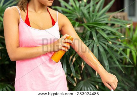 Woman spraying mosquito insect repellent on arm skin outdoor in nature forest. poster
