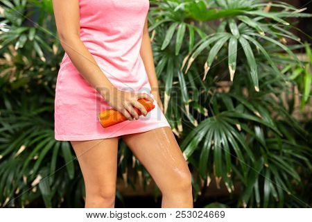 Woman spraying mosquito insect repellent on leg outdoor in nature forest. poster