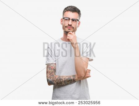 Young tattooed adult man with hand on chin thinking about question, pensive expression. Smiling with thoughtful face. Doubt concept.