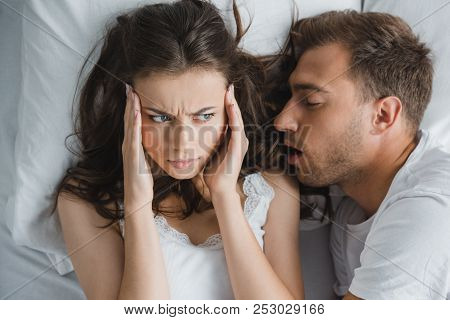 Top View Of Young Woman With Headache Looking At Husband Snoring In Bed