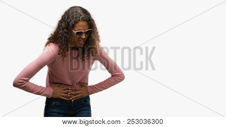 Beautiful young hispanic woman wearing sunglasses with hand on stomach because indigestion, painful illness feeling unwell. Ache concept.
