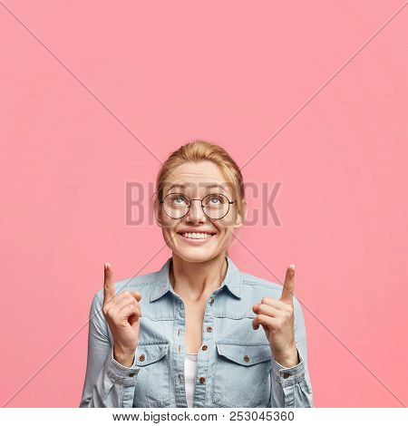 Vertical Shot Of Delighted Pretty Blonde Young Woman Has Pleasant Appearance, Indicates Upwards With