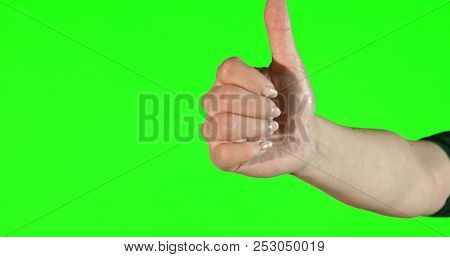 Female hand gestures on green screen: thumbs up.