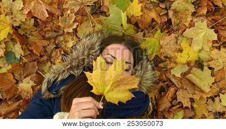Young woman lying in autumn park with leafs.