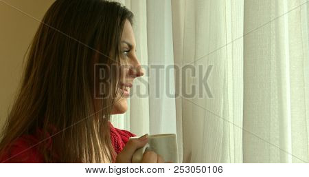 Woman enjoying her morning coffee or tea, Looking out the window. Beautiful romantic girl drinking hot beverage.