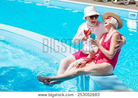 Retired Man And Woman Laughing While Sunbathing Near Pool