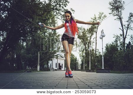 Excited Girl Dancing And Listening Music Smart Phone In The Street. Young Beautiful Student Goes And