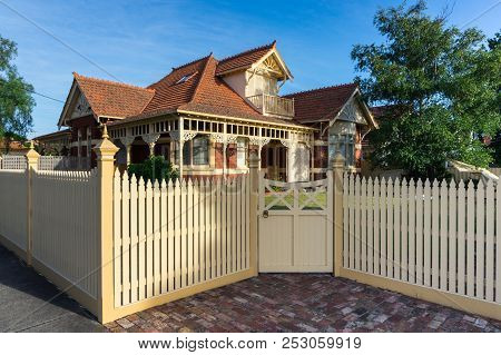 Melbourne, Australia - February 17, 2018: A Brick Heritage Home With A White Wooden Picket Fence In