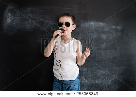 Young Boy's Standing Near Blackboard Singing In Microphone. Rockstar. Creative Design Concept Of Fut