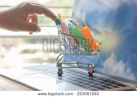 Hand Pushes Colorful Shopping Paper Bags In Blue Trolley On Laptop Keyboard Which Has Cloud On Scree