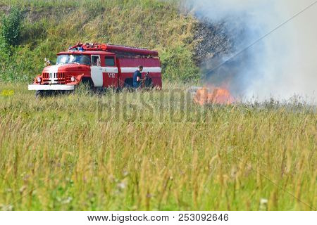 Fire Truck And Firefighter On Firefighting Rescue Operation Fighting With Flames In Burning Meadow I